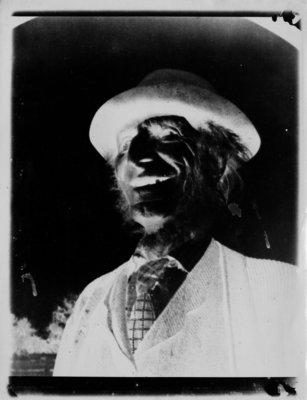Negative print of bust portrait of laughing man wearing a hat with rolled brim.