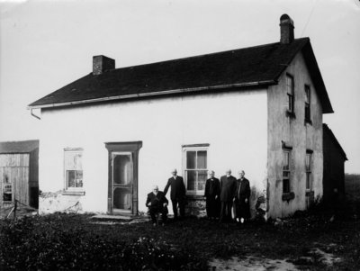Group portrait of 5 elderly people [3 men, 2 women], in front of a storey and half stucco house.