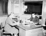 Unidentified Woman and Man Sitting at an Office Desk