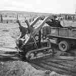 Crawler Tractor Loading Dirt into Dump Truck