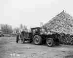 Tractor With a Homemade Cab Next to Lumber Pile