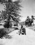 Unidentified Man Driving Down Dirt Road on a Tractor, Waterdown, ON