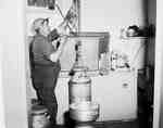 Man Using a Pulley to Lift Milk Can into Cooler