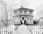 Unidentified Family Posing for Photo Outside House