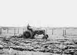 Man Ploughing [Plowing] a Field With Town in the Background