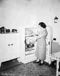 Unidentified Woman Standing in Kitchen with Fridge Door Open, Englehart, ON