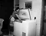 Unidentified Woman Looks into a Freezer