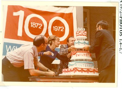 Three people adding layers to the Centennial cake