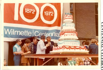 People on a stage with Centennial cake
