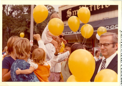 Street scene with people holding baloons