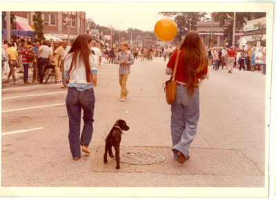 Two girls walking a puppy in the street