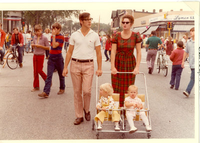 Man and woman pushing a stroller with two children