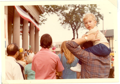 Child on his parents shoulders