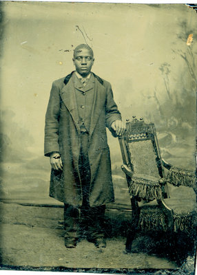 Tintype of African American Man in Topcoat Standing with Chair [n.d.]