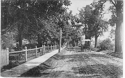 Water Street, Burlington, Ont. -- view of car driving along fenced road; postmarked August 25, 1913