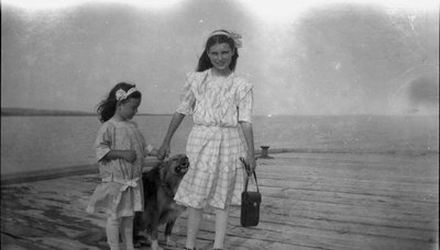 Two young girls and a happy dog on a wharf