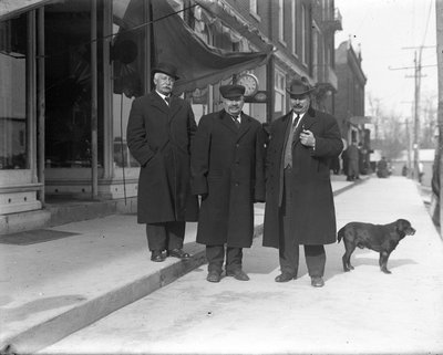 Three men standing in front of a jewellery store, King Street, Colborne