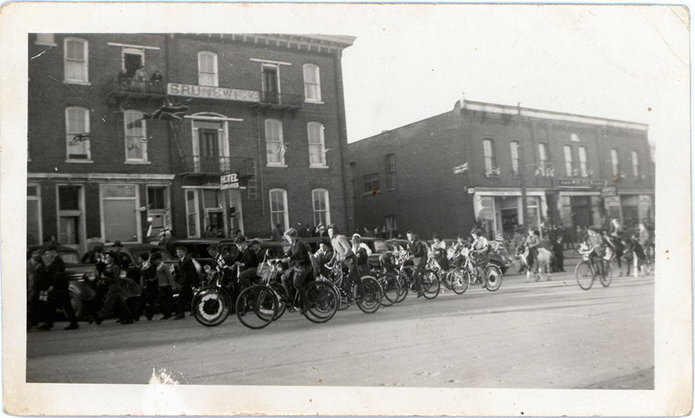 Photograph of bike parade in front of Brunswick Hotel, Colborne, Cramahe Township
