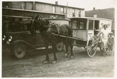 Everet Rowsome, Mrs. Rowsome and Charles in front of a Rowsome's Bakery horse drawn wagon and a Rowsome's Bakery Truck, Colborne