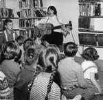 Georgetown Public Library - Librarian Anne Anderson entertaining children by singing and playing guitar.