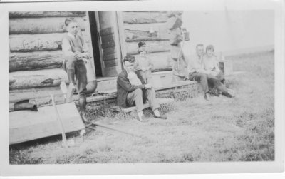 Group of people sitting by log cabin