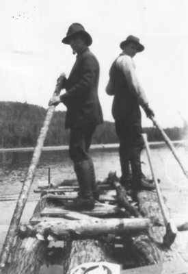 Two men men standing on raft in small lake near Otter Cove.