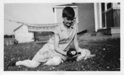 Young Girl Sitting on Lawn Feeding a Cat