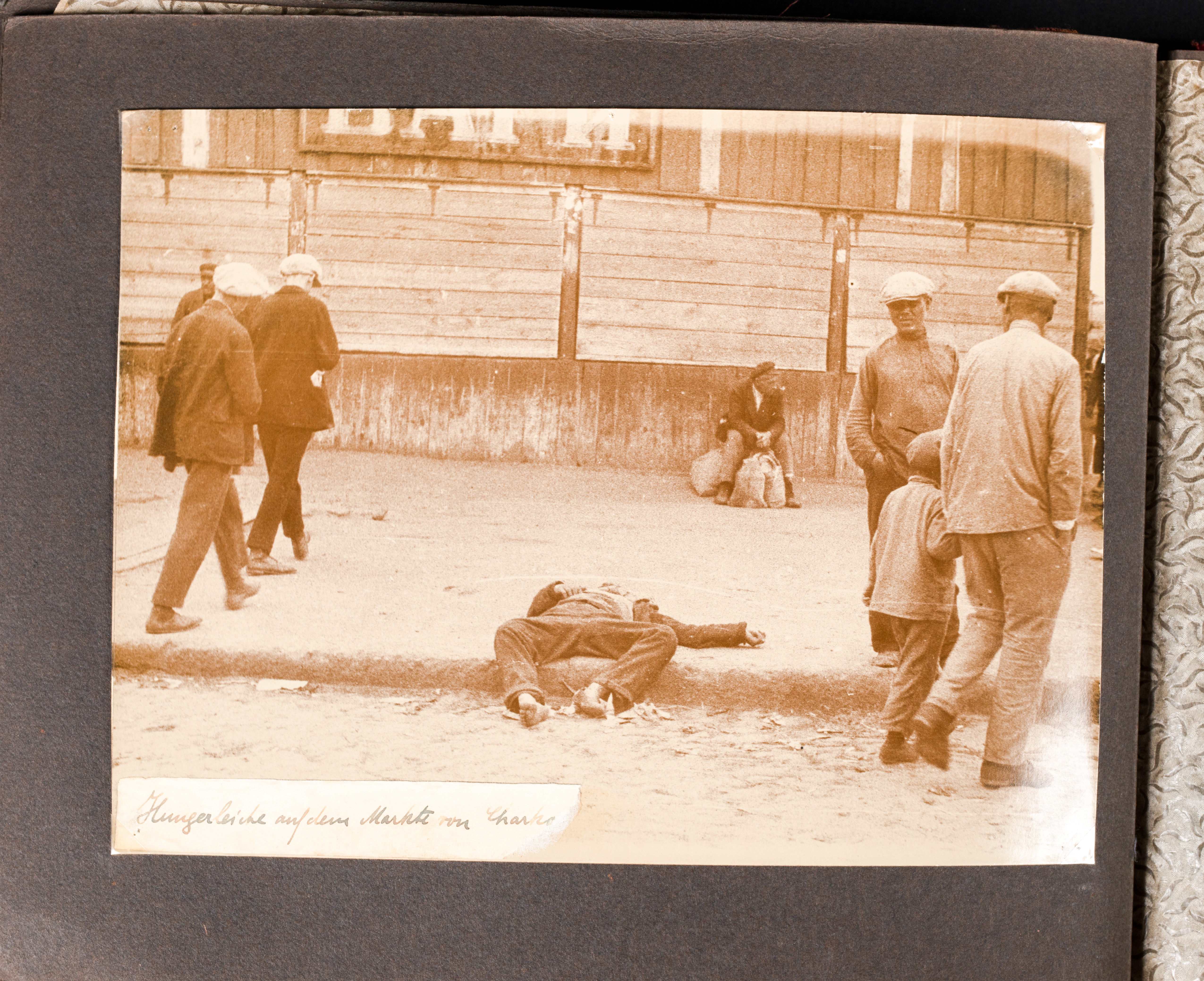 A famine victim lies dead near a market in Kharkiv with some men pausing to look while others pass by
