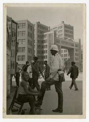 A traffic officer is getting a shoeshine from a young boy with the new Kharkiv government buildings in the background