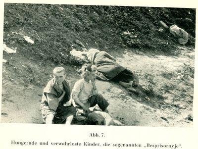 Two destitute children sit near a sleeping woman by a grassy embankment in Kharkiv