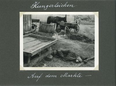 A farm woman, victim of starvation, lies behind a cart near a marketplace in Kharkiv