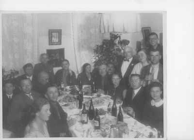 Several men and women pose around a dinner table laden with food and drinks