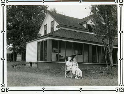 Farmhouse at Fairyport, Fairy Lake, Huntsville, Ontario. Northwest side looking toward the lake in the 1930's. Guests seated in front.
