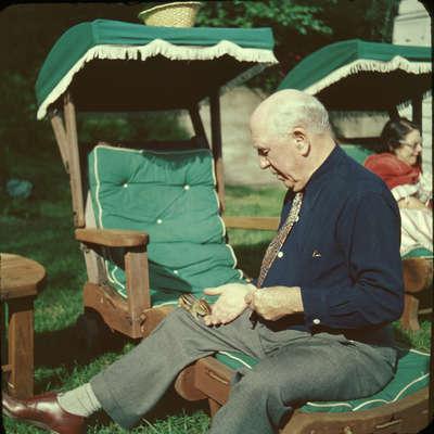 Dr. Edgar Evans, feeding a chipmunk, Huntsville, Ontario, 1951.  Wife Hilda in background.