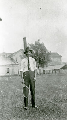 Man with tennis racket at the rear of Doon Twines building, Doon, Ontario