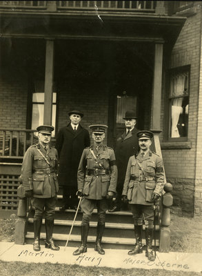 Three officers and two civilians standing at entrance to house