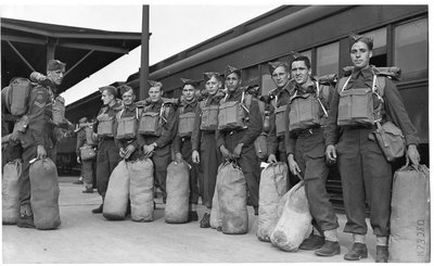 World War II:  Unidentified group of soldiers with army packs and gear at train station, London, Ontario