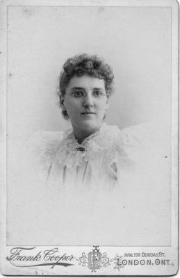 Portrait of an unidentified young woman with curly hair, wearing glasses, London, Ontario