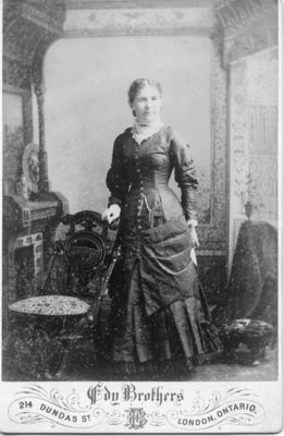 Portrait of an unidentified woman wearing a dark coloured dress with a white high neck collar, London, Ontario