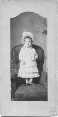 Portrait of an unidentified young girl dressed formally and standing on a chair.