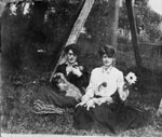 Two ladies sitting by by trees with dog and puppies.