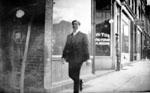 Man walking past stores on Main St., Milton.