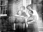 Four women posed in front of door