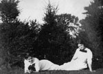 Two women in white dresses seated on ground