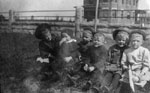 Young lady with five little children sitting in a row