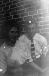 Man and woman posed by brick wall