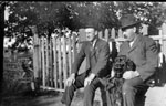 Two men and dog sitting by fence