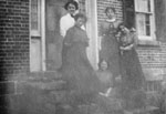 Five women posed on doorstep of brick house