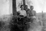 Two men and one young woman posed by tree