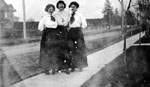 Three young ladies standing on sidewalk